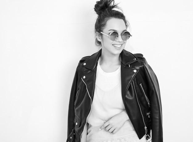 Portret van het jonge mooie donkerbruine model van het vrouwenmeisje met naakte make-up die de kleren van het de leerjasje van de de zomer hipster fietser in zonnebril dragen die dichtbij muur stellen.