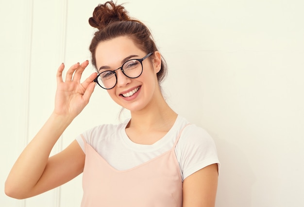 Portret van het jonge mooie donkerbruine model van het vrouwenmeisje met naakte make-up in de kleurrijke kleren die van de zomer roze hipster dichtbij muur stellen. gelukkig kijken