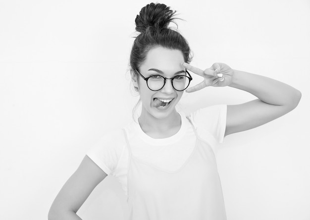 Portret van het jonge mooie donkerbruine model van het vrouwenmeisje met naakte make-up in de kleurrijke kleren die van de zomer roze hipster dichtbij muur stellen. haar tong en vredesteken tonen