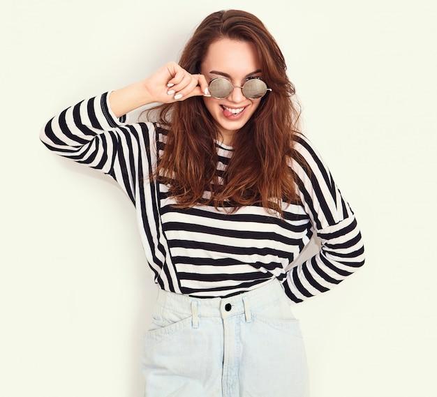 Portret van het jonge mooie donkerbruine model van het vrouwenmeisje met naakte make-up in de zomer hipster kleren en zonnebril die dichtbij muur stellen. toont haar tong