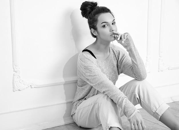Portret van het jonge mooie donkerbruine model van het vrouwenmeisje met naakte make-up in de zomerkleren die dichtbij muur stellen. zittend in de vloer