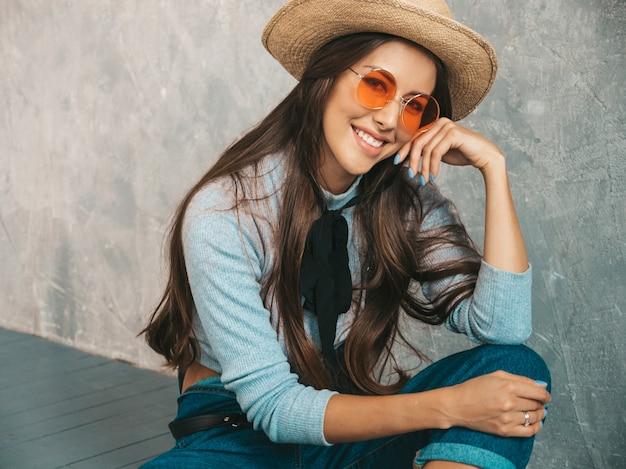 Portret van het jonge mooie glimlachende vrouw kijken. trendy meisje in casual zomer kleding en hoed. in zonnebril. op de vloer zitten