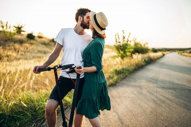 Portret van het jonge paar kussen op het natuurlijke landschap. lopen op elektrische scooters op het platteland