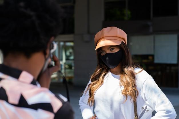 Portret van het jonge paar toeristen die beschermend masker dragen en camera gebruiken tijdens het nemen van foto's in de stad. toerisme concept. nieuw normaal levensstijlconcept.
