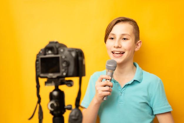 Portret van het jonge tienerjongen zingen over de microfoon die op geel wordt geïsoleerd