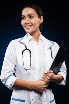 Portret van het jonge vrolijke klembord van de artsenholding en opzij het kijken
