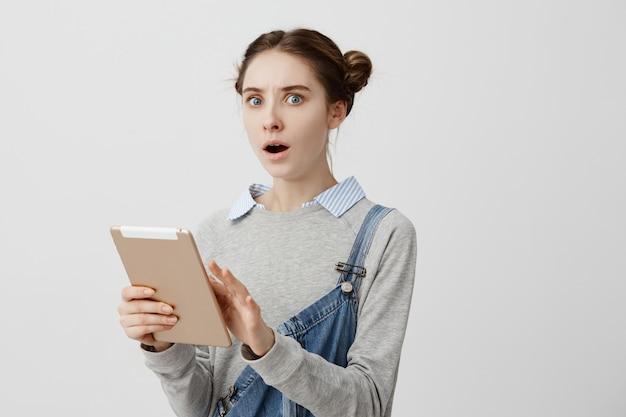 Portret van het jonge vrouw kijken uitdrukkend spanning en vrees die gouden tablet houden. gefrustreerde vrouwelijke receptioniste besefte dat ze haar baasschema in de war bracht. negatieve emoties