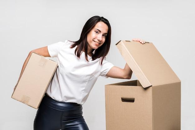 Portret van het jonge vrouw stellen met dozen