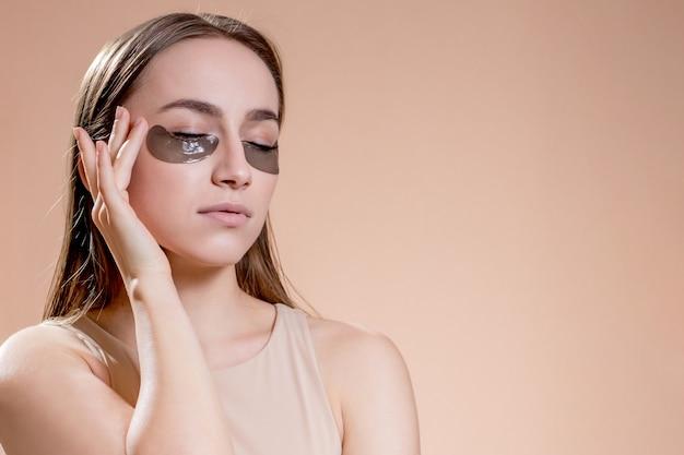 Portret van het jonge vrouw stellen met toegepaste zwarte schoonheidsflarden onder ogen over beige achtergrond