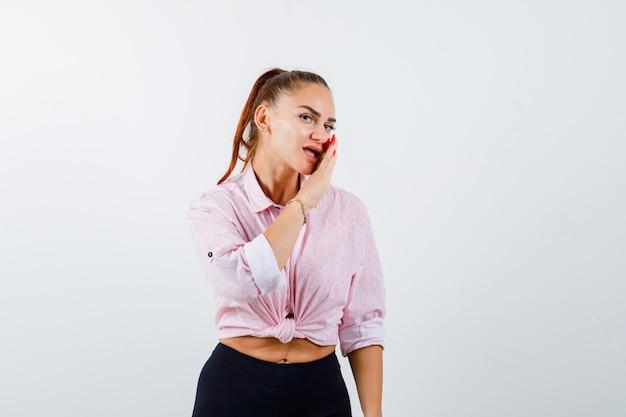 Portret van het jonge vrouwelijke geheim achter hand in casual shirt, broek en op zoek naar mooi vooraanzicht