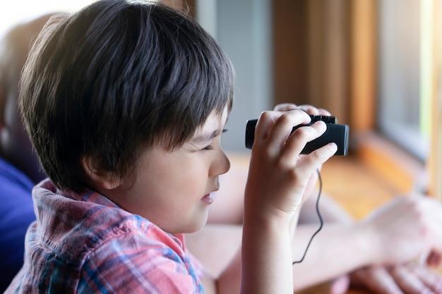 Portret van het kind die van de jong geitjejongen door van verrekijkers in het de meningspunt bekijken van de dierenpost