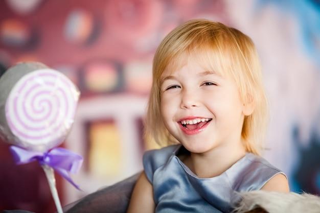 Portret van het kleine blonde glimlachende meisje spelen met stuk speelgoed suikergoed. kerstmis en nieuwjaar thema