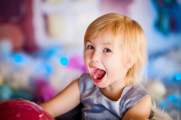 Portret van het kleine blonde glimlachende meisje spelen met stuk speelgoed suikergoed.
