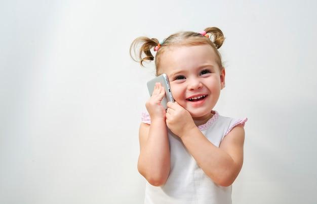 Portret van het kleine meisje positief dat praten over een telefoon