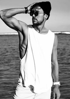Portret van het knappe hipster zonnebaadde model van de maniermens die vrijetijdskleding in witte t-shirt dragen en zonnebril die op blauwe oceaan en hemel stellen