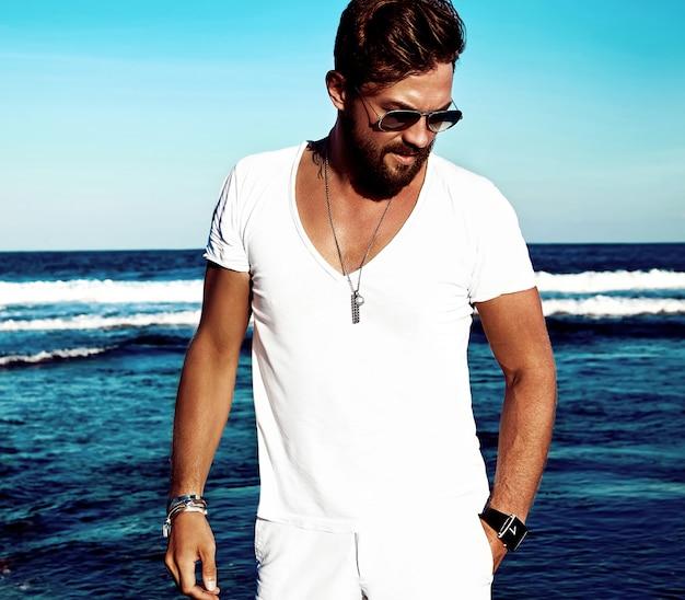 Portret van het knappe model die van de maniermens witte kleren dragen die op blauwe overzees stellen