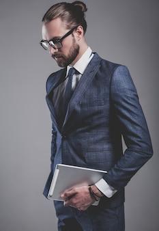 Portret van het knappe model van de manierzakenman gekleed in elegant blauw kostuum met glazen