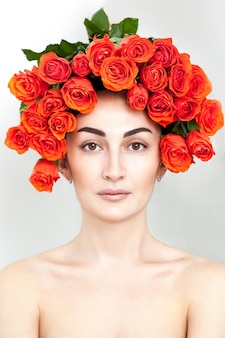 Portret van het lachende roodharige meisje met oranje rozen