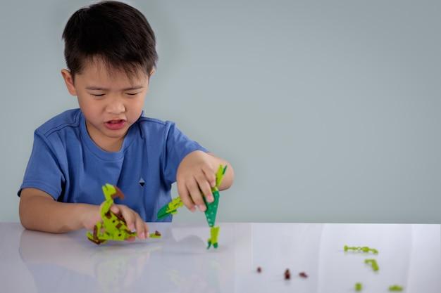 Portret van het leuke aziatische jongen spelen met kleurrijke plastic stuk speelgoed bakstenen