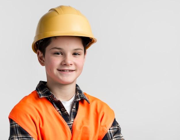 Portret van het leuke jonge jongen stellen met bouwvakker