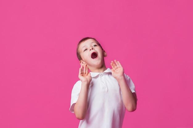Portret van het leuke jongen gillen met mond open op roze achtergrond