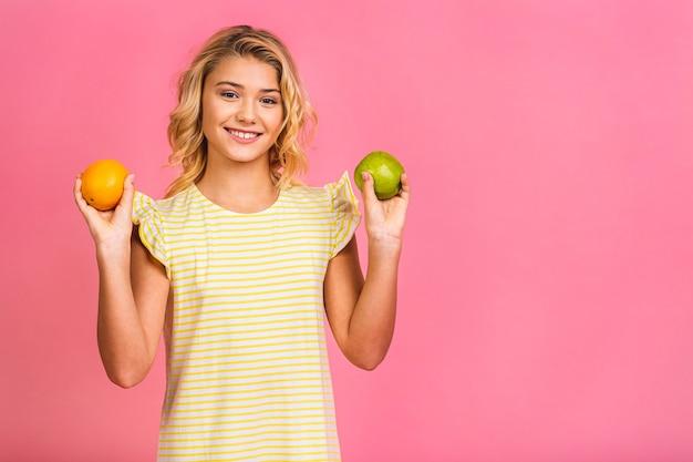 Portret van het leuke kleine meisje dat van het tienerkind een appel houdt