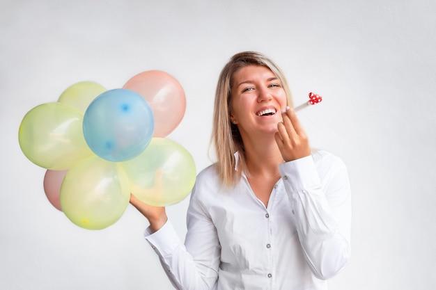 Portret van het meisje dat heel wat ballons heeft die een feestelijk fluitje houden