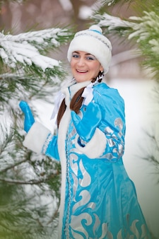 Portret van het meisje in een pet in de winter in het bos