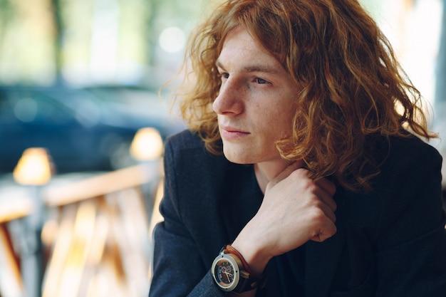 Portret van het modieuze roodachtige jonge mens stellen