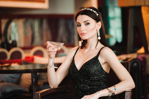 Portret van het mooie glas van de vrouwenholding van martini.