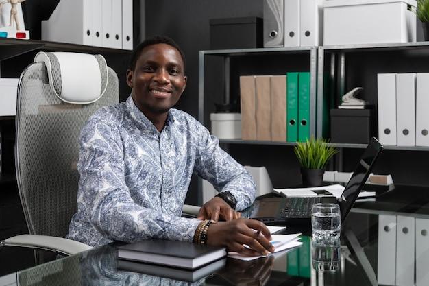 Portret van het mooie jonge afrikaanse amerikaanse zakenman werken met documenten en laptop in bureau