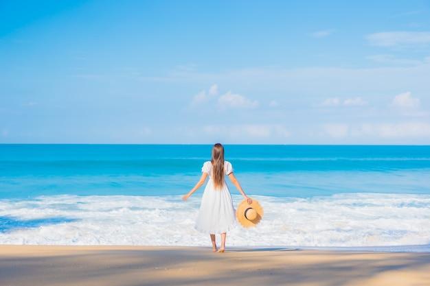Portret van het mooie jonge aziatische vrouw ontspannen rond strand met witte wolken op blauwe hemel in reisvakantie