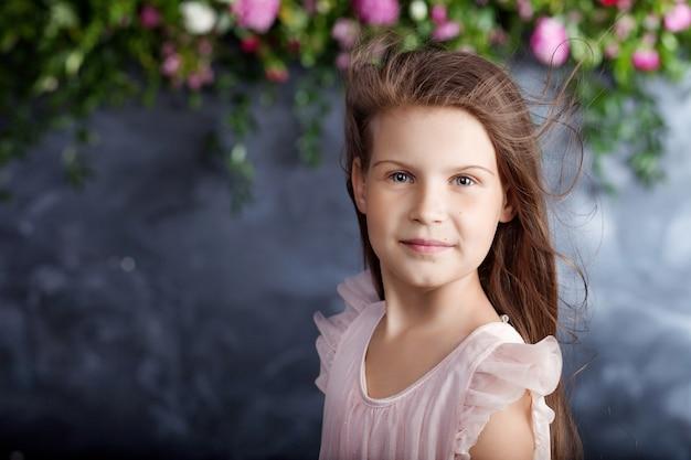 Portret van het mooie kleine meisje met een boeket bloemen. wind in haar