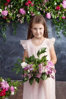 Portret van het mooie kleine meisje met een boeket bloemen.