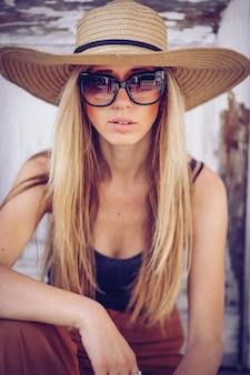 Portret van het mooie koele meisje gesturing in hoed en zonnebril over grungemuur