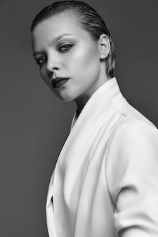 Portret van het mooie model van de manier modieuze donkerbruine vrouw met avondmake-up en rode lippen in wit jasje