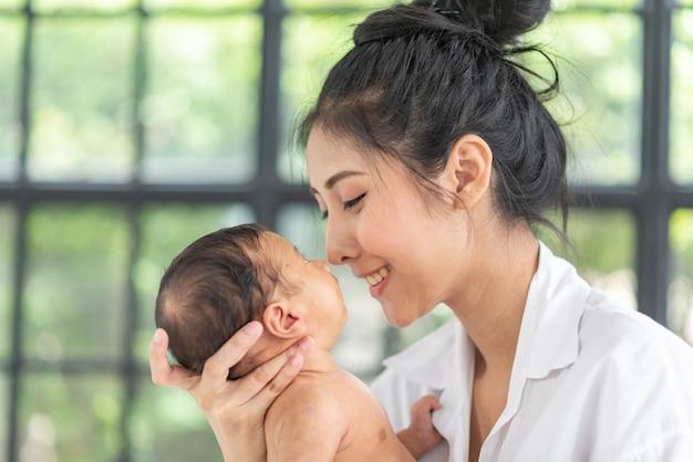 Portret van het mooie moeder spelen met haar 1 maanden oud baby in het bed