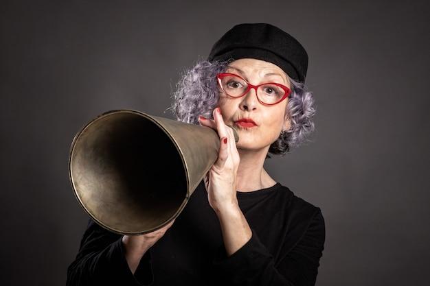 Portret van het mooie oudere vrouw schreeuwen met een oude megafoon op grijs