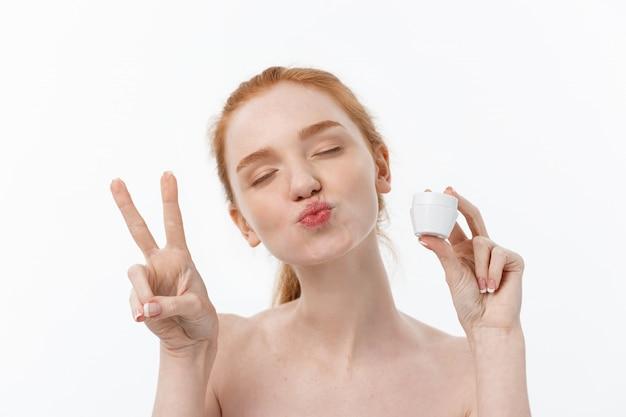 Portret van het mooie vrouw glimlachen terwijl het nemen van wat die gezichtsroom op witte achtergrond met exemplaarruimte wordt geïsoleerd.