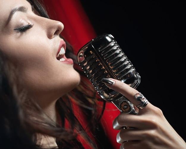 Portret van het mooie vrouw zingen in microfoon