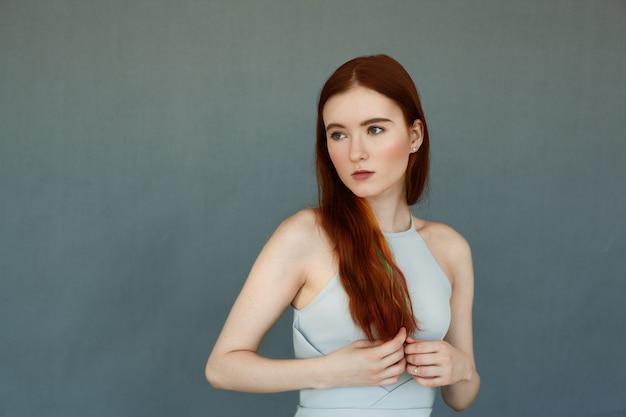 Portret van het mooie vrouwelijke model met rood lang haar en schitterende groene ogen tegen blauwe bakstenen muur. aantrekkelijke jonge vrouw die weg kijkt met doordachte en dromerige uitdrukking