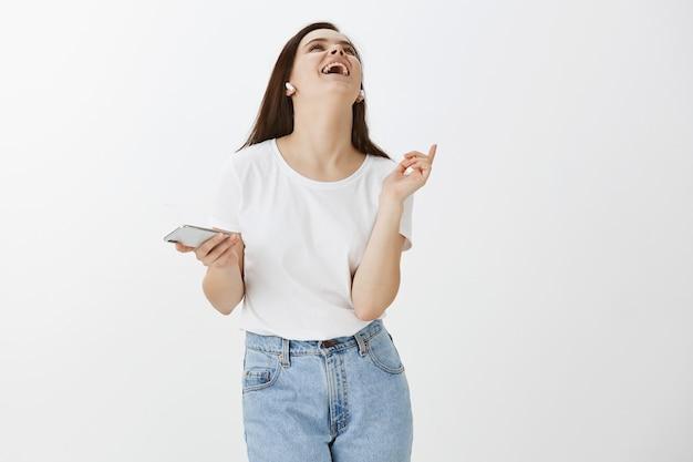 Portret van het onbezorgde jonge vrouw stellen met haar telefoon en oordopjes tegen witte muur
