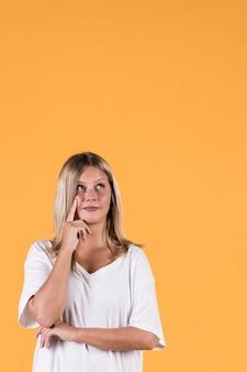 Portret van het overwegen van jonge vrouw die omhoog kijkt