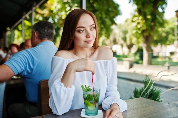 Portret van het overweldigende jonge vrouw stellen met mojitococktail in koffie naast het park.