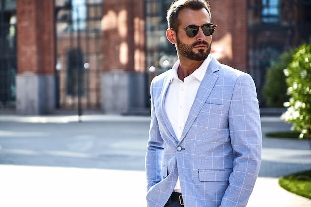 Portret van het sexy knappe model van de manierzakenman gekleed in het elegante blauwe kostuum stellen op straatachtergrond. metrosexual