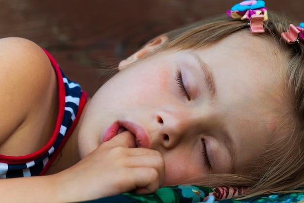 Portret van het slapende mooie kindmeisje dat haar vinger zuigt tijdens het slapen.