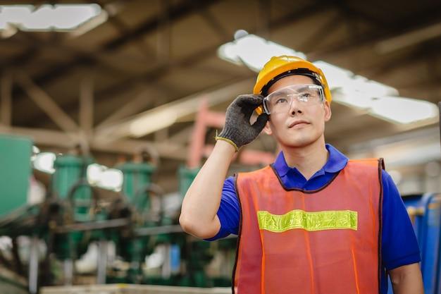 Portret van het slimme knappe model van ingenieursaziatische chinese gelukkige arbeidsarbeider in zware industrie