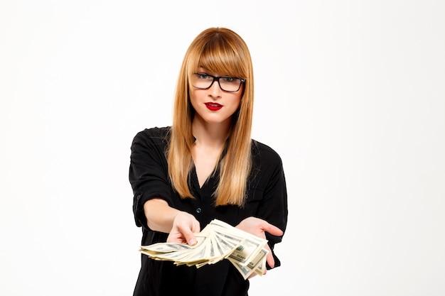 Portret van het succesvolle geld van de onderneemsterholding over witte muur