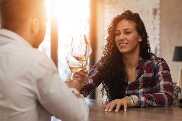 Portret van het verliefde jonge paar roosteren met witte wijn. lens flare