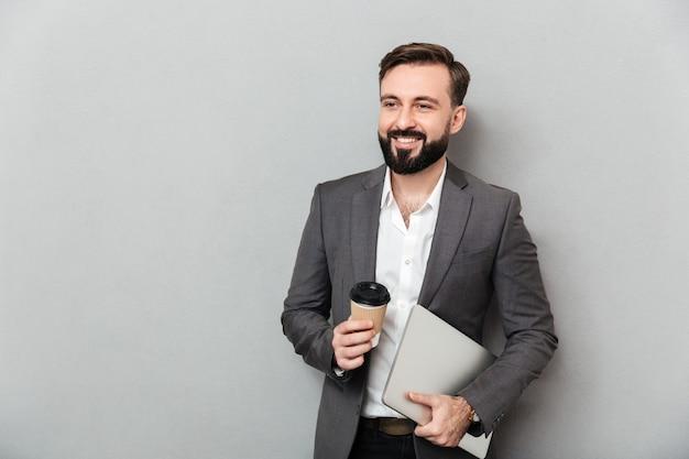 Portret van het vrolijke mannelijke beambte stellen op de meeneemkoffie van de cameraholding en zilveren laptop, geïsoleerd over grijze muur